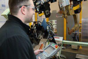 Robot technician using teach pendant to program robot.